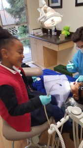 Aspiring dentist helping with sister's appointment